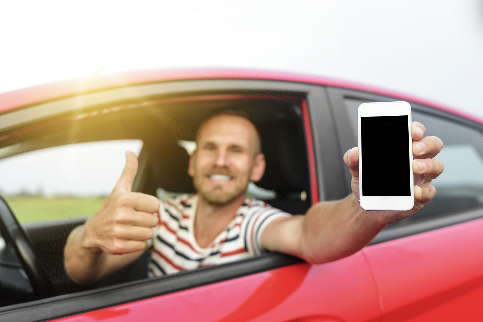 A man in a car with smartphone