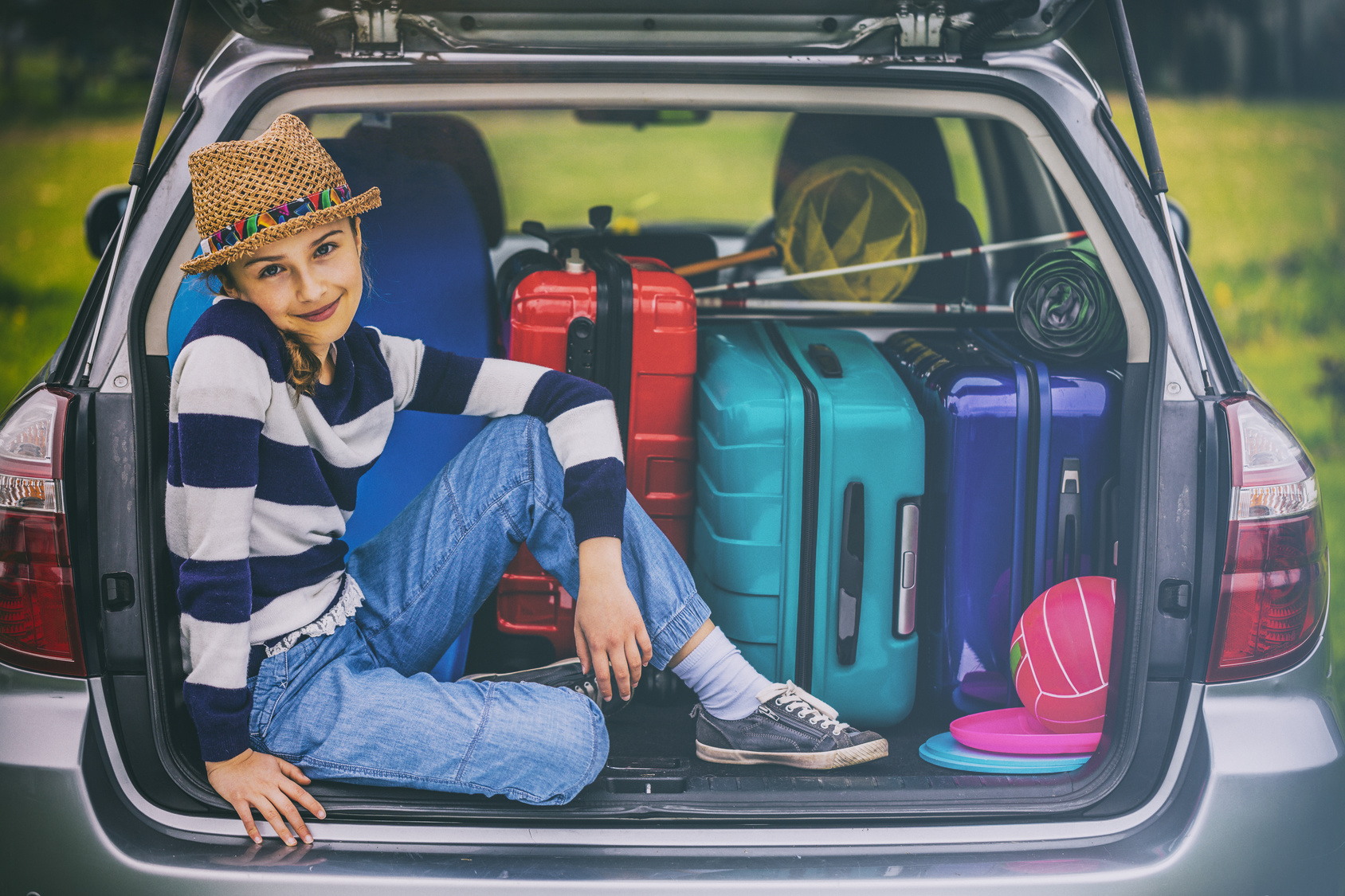 A hip girl in a car trunk looks happy.